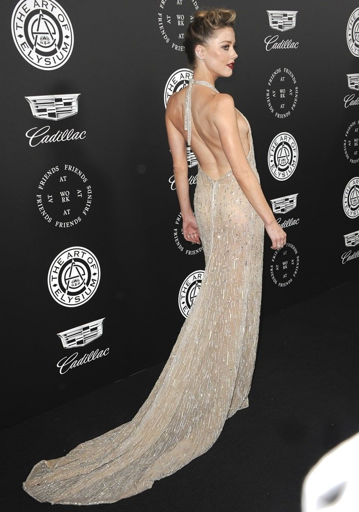Amber Heard wearing a low-cut silver dress at the 2018 Art of Elysium Heaven Gala in Santa Monica, California, on January 6, 2018
