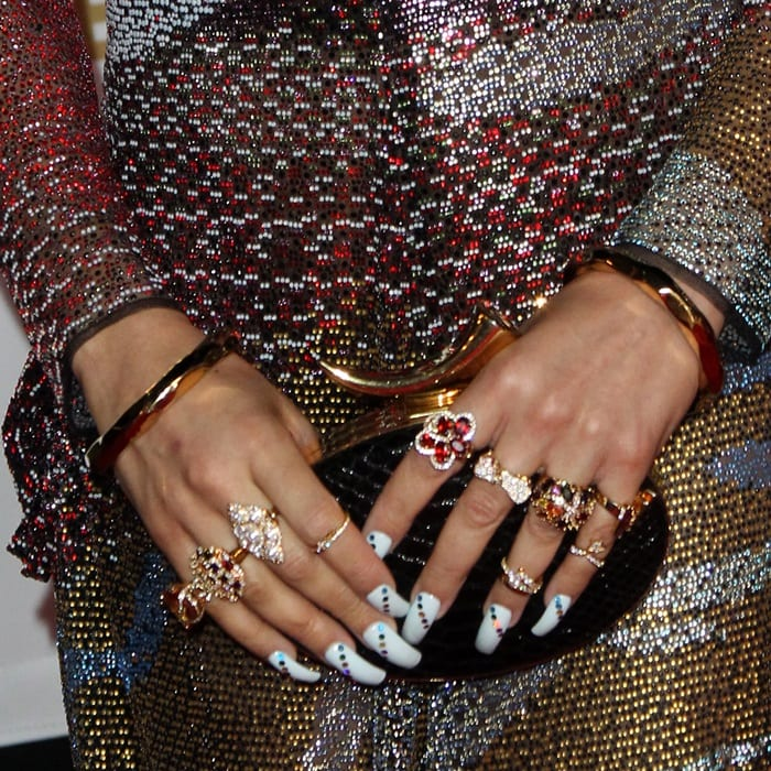 Andra Day showing off her Giuseppe Zanotti clutch and rings