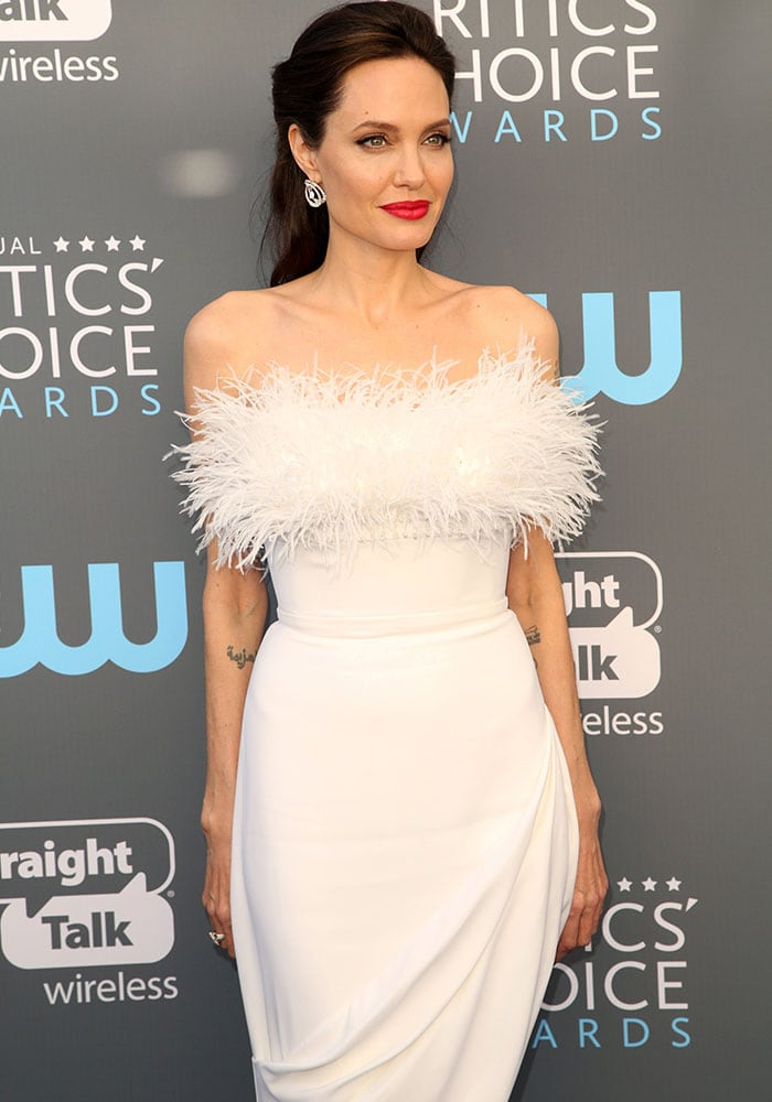 Angelina contrasts a bold red lip against her stark white dress