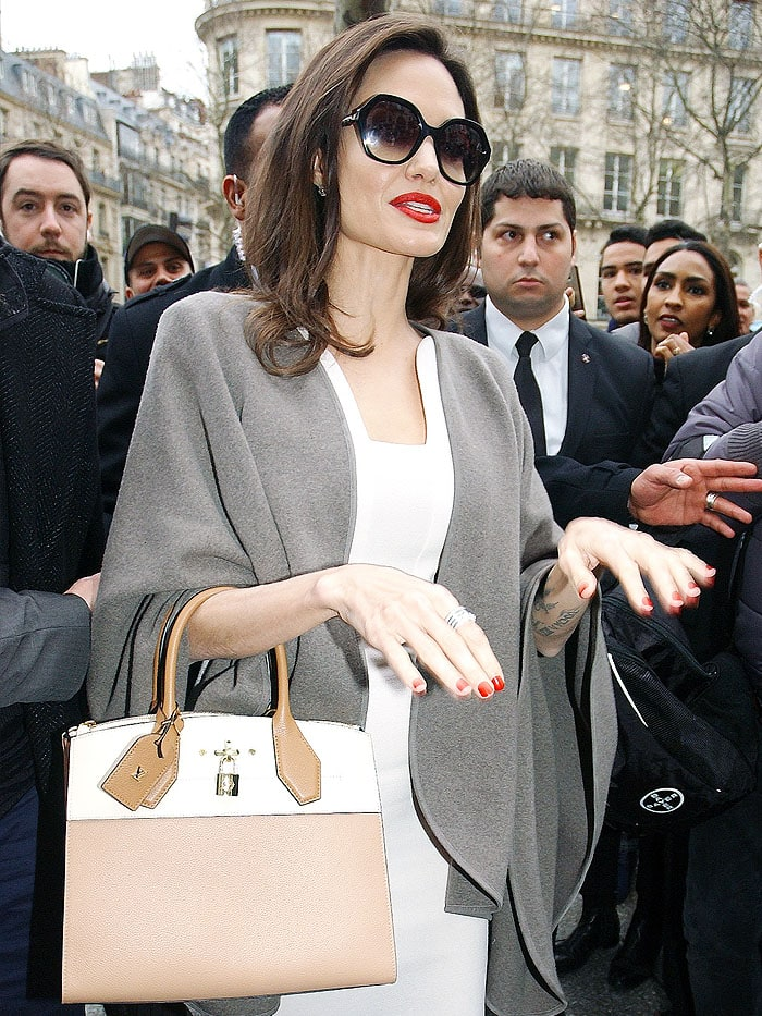 Angelina Jolie protected her shoulders with a gray cape and covered her peepers with Fendi oversized sunglasses