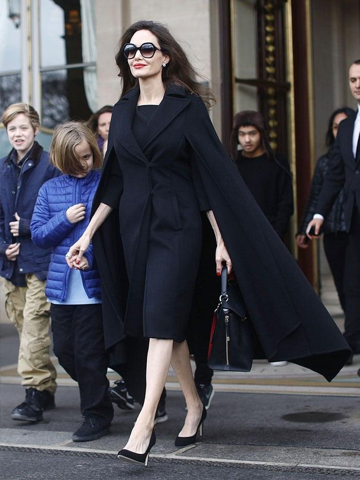 Angelina Joliecut a stylish figure in an Elie Saab caped coat, a Salvatore Ferragamo large top-handle bag, and her trusty Fendi sunglasses