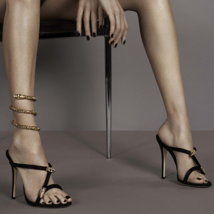 "Bella Hadid wearing statement-making ""Aleesha"" sandals featuring golden hardware and a complementary serpent-shaped anklet"