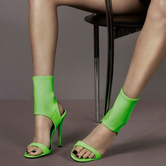 "Bella Hadid wearing lime green neoprene ""Agnes"" sandals featuring a cut-out stiletto"
