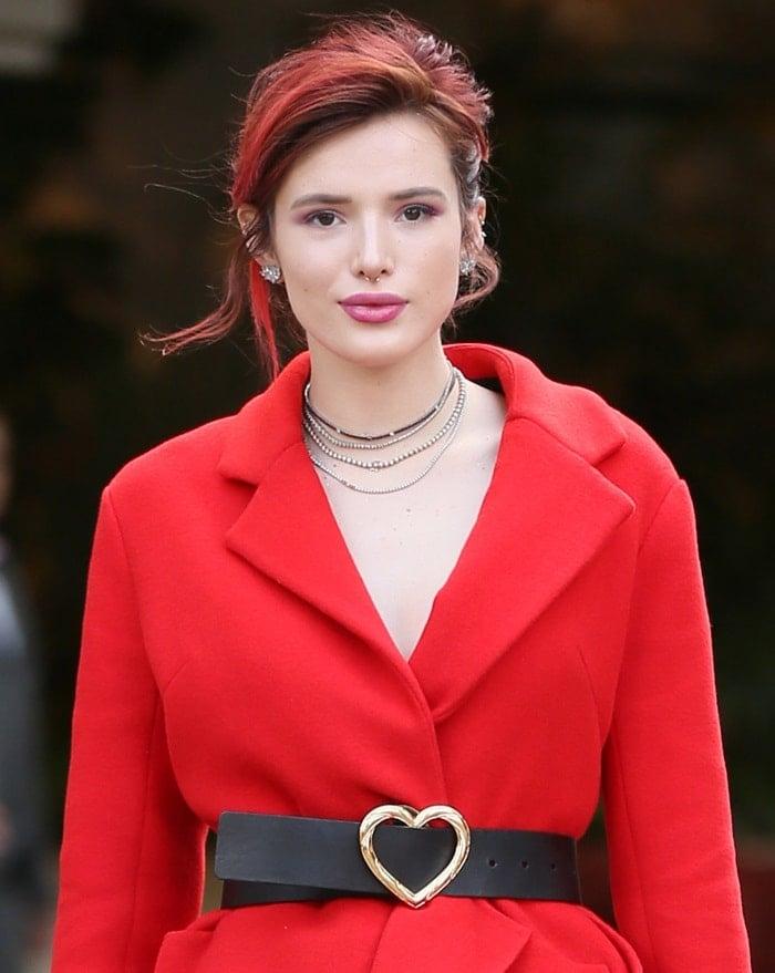 Bella Thorne'sred coat and a heart-detailed black belt