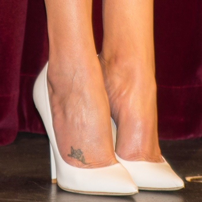 Charlize Theron in white pointy-toe shoes that exposed her floral foot tattoo