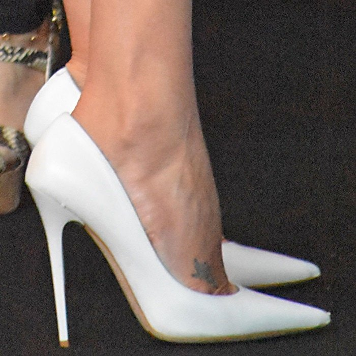 Charlize Theron wearing white pointy-toe pumps