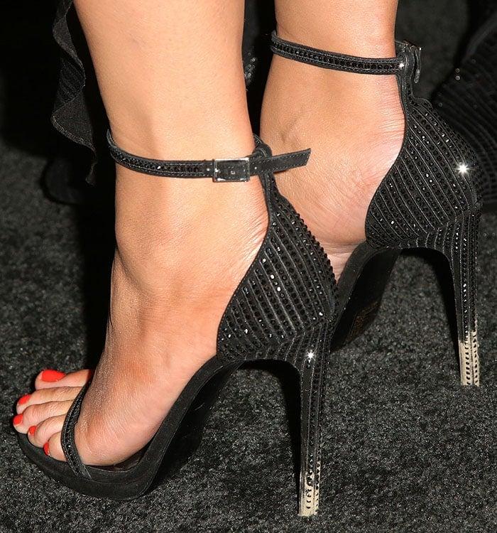 Closeup of the muddy heels on Chrissy Teigen's Saint Laurent 'Jane' crystal-studded ankle-strap sandals.