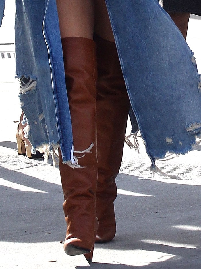 Closeup of Chrissy Teigen's Saint Laurent 'Niki' thigh-high boots in cognac leather.