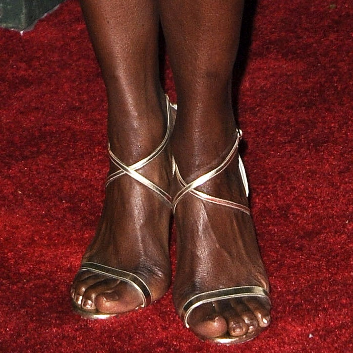 "Danai Gurira's feet in gold Jimmy Choo ""Hesper"" crisscross-strap sandals"