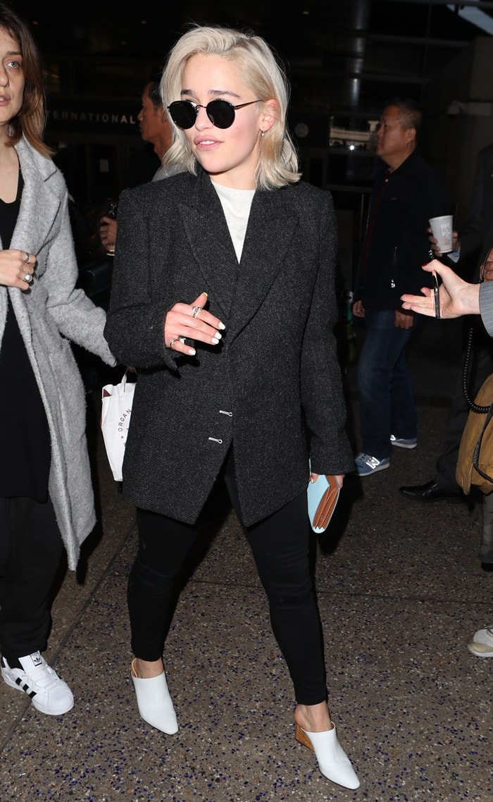 Emilia Clarke arriving at LAX airport in a black jacket and tight leggings