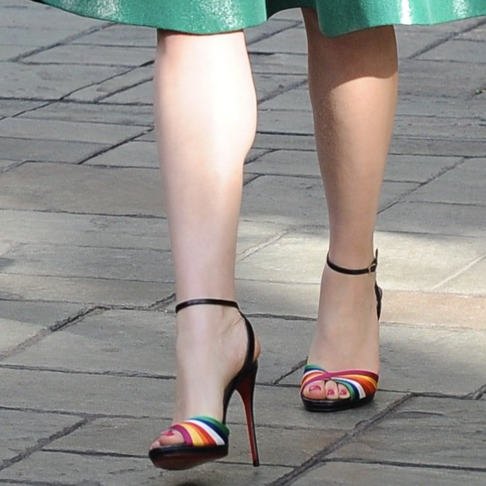 Emilia Clarke wearing Christian Louboutin's Naseeba sandals that are assembled from black nappa leather and multicolored satin