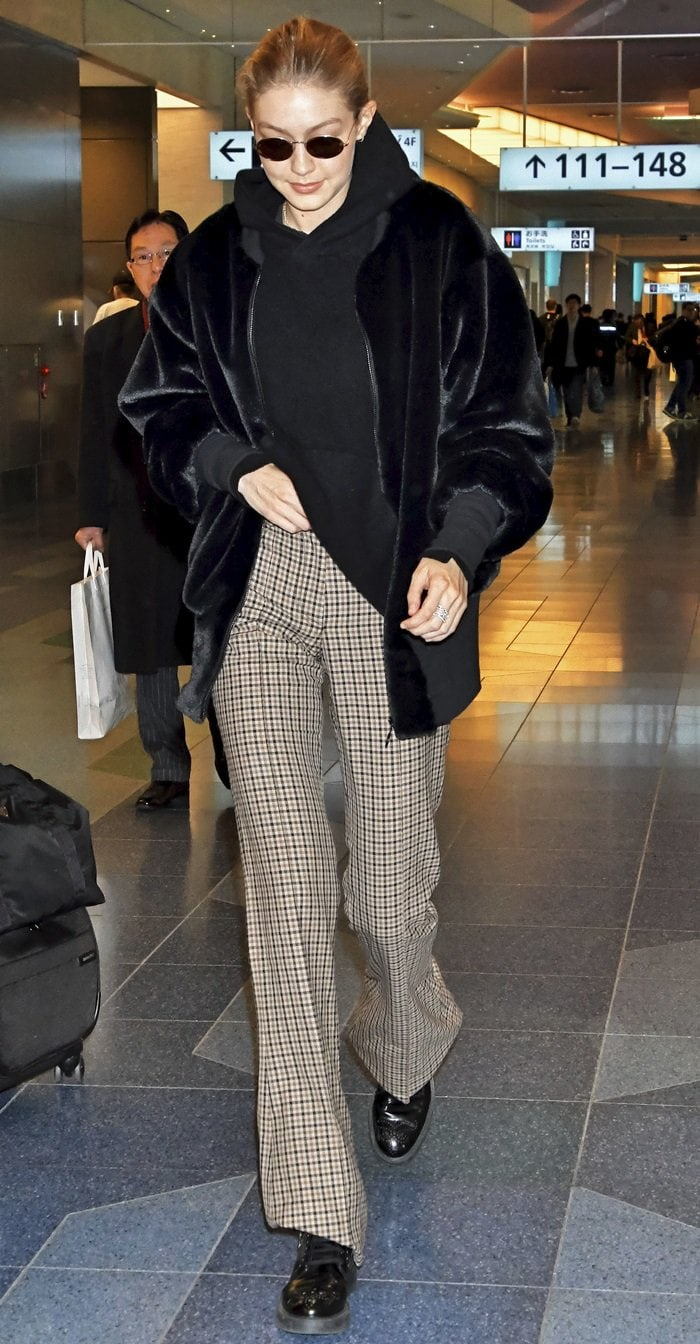 Gigi Hadid wearing patterned bell-bottom pants paired with a 'Teddy' stretch cotton-trimmed faux shearling bomber jacket from House of Fluff at Tokyo International Airport on January 26, 2018