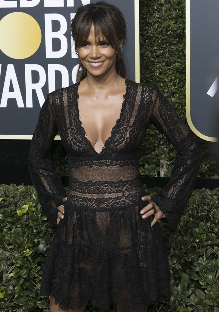 Halle Berry finished her red carpet look off with Swarovski earrings, a Maxior ring, and a black diamond and emerald ring by AS29