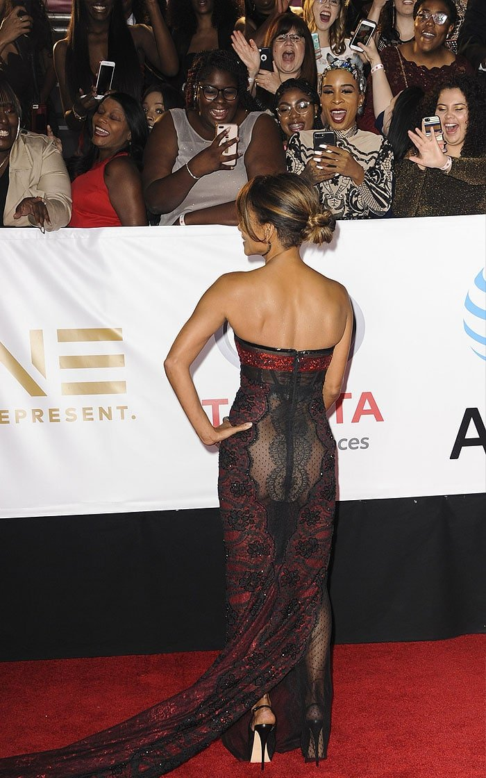 Halle Berry showing that she's gone commando underneath her red-and-black lace gown to the crowd, who seems to love it.