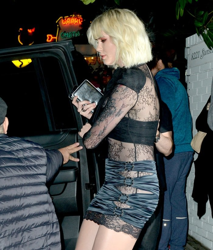 Ireland Baldwin put on a very leggy display in a black silk bow detail lace dress from Faith Connexion
