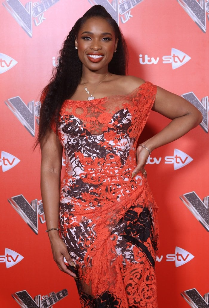 Jennifer Hudson wearing an orange, black, and white off-the-shoulder lace dress from the Vivienne Westwood Spring 2016 Collection