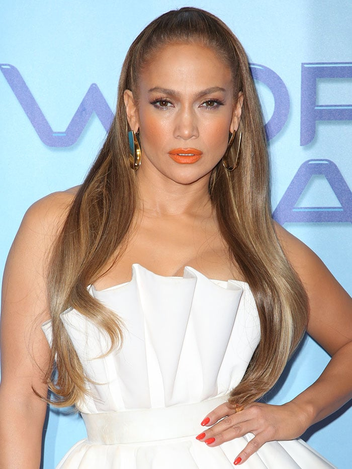 Jennifer Lopez added touches of color to her leg-flaunting frock with orange lips, orange nails, gold loop earrings and a gold cuff bracelet