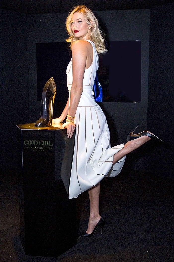 Karlie Kloss with a Good Girl perfume bottle shaped like a curvy black pump
