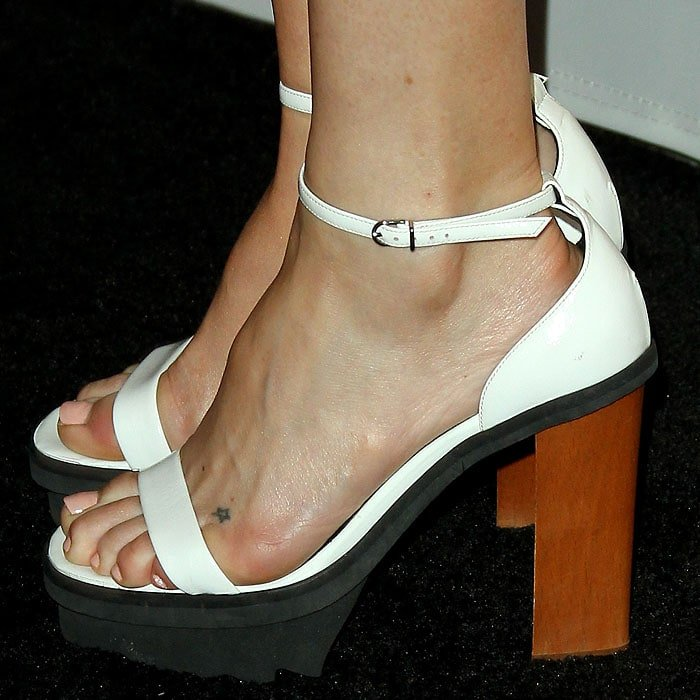 Details of the white chunky ankle-strap platform sandals with black ripple soles and wooden heels on Kate Hudson.
