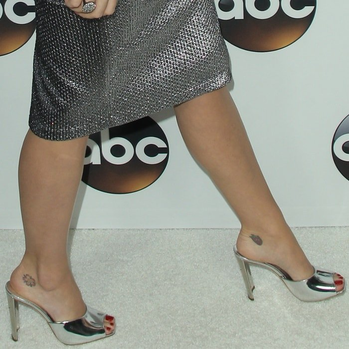 Katy Perry showing off her foot tattoos in Giuseppe Zanotti's SS18 silver mirror leather 'Haileen' mules with metal heels