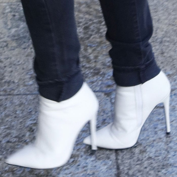 Closeup of the Kurt Geiger 'Ride' white leather booties on Kylie Minogue.