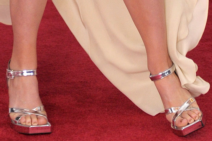 Closeups of Lana Del Rey's too big silver Gucci platform sandals with square toes.