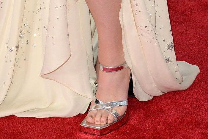 Closeups of Lana Del Rey's too big silver Gucci platform sandals with square toes.