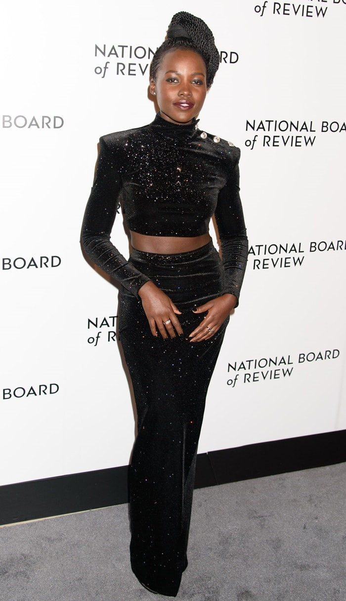 Lupita Nyong'o sported a long-sleeve crop top with silver button detailing on one shoulder, a pencil maxi skirt, jewelry from Dana Rebecca Designs, and Jimmy Choo shoes