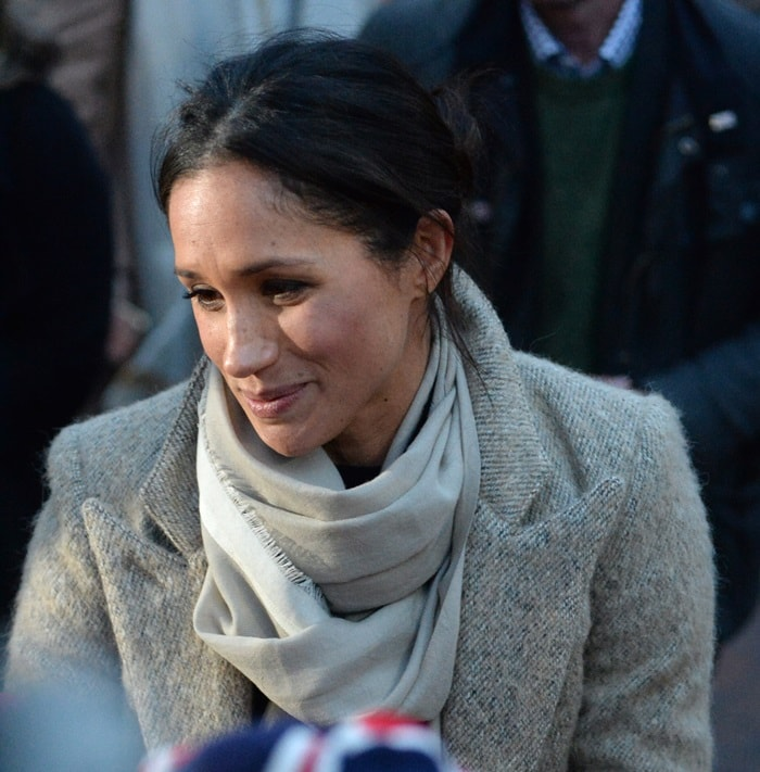 Meghan Markle wearing a beautiful Smythe coat with a multi-wrap scarf