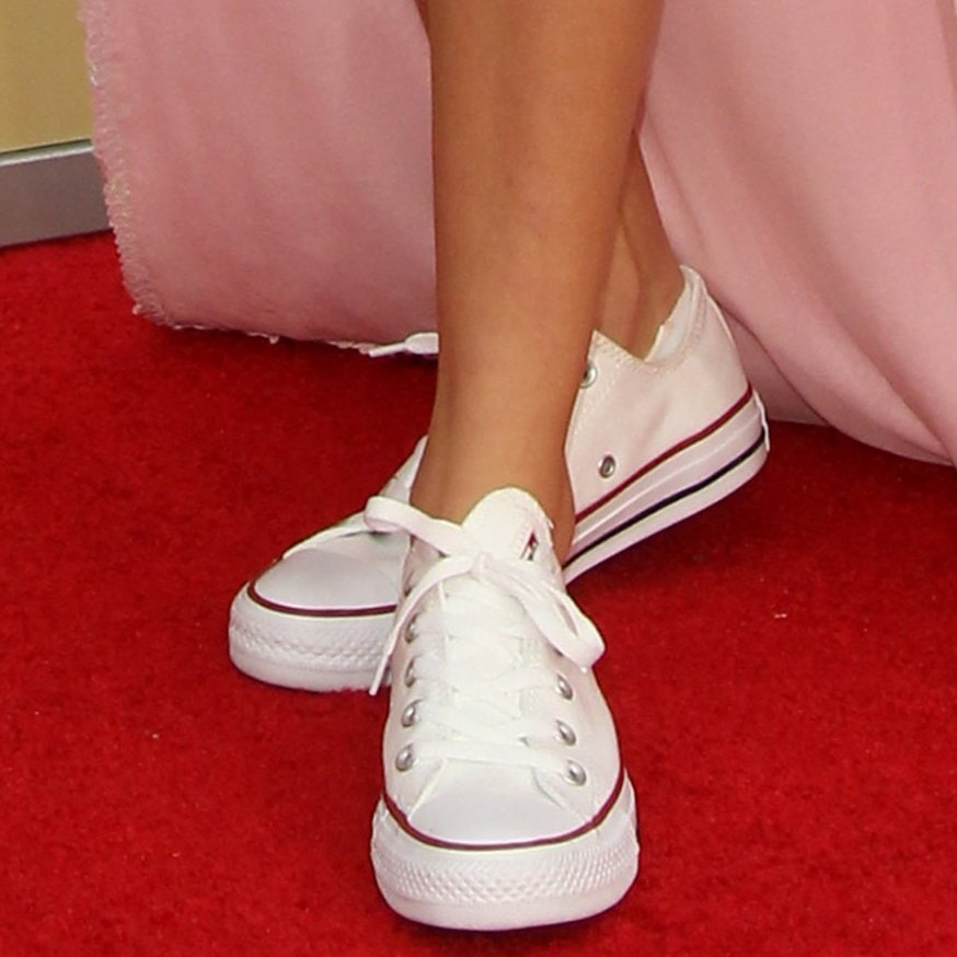 Millie Bobby Brown wearing classic Converse Chuck Taylor All Star sneakers