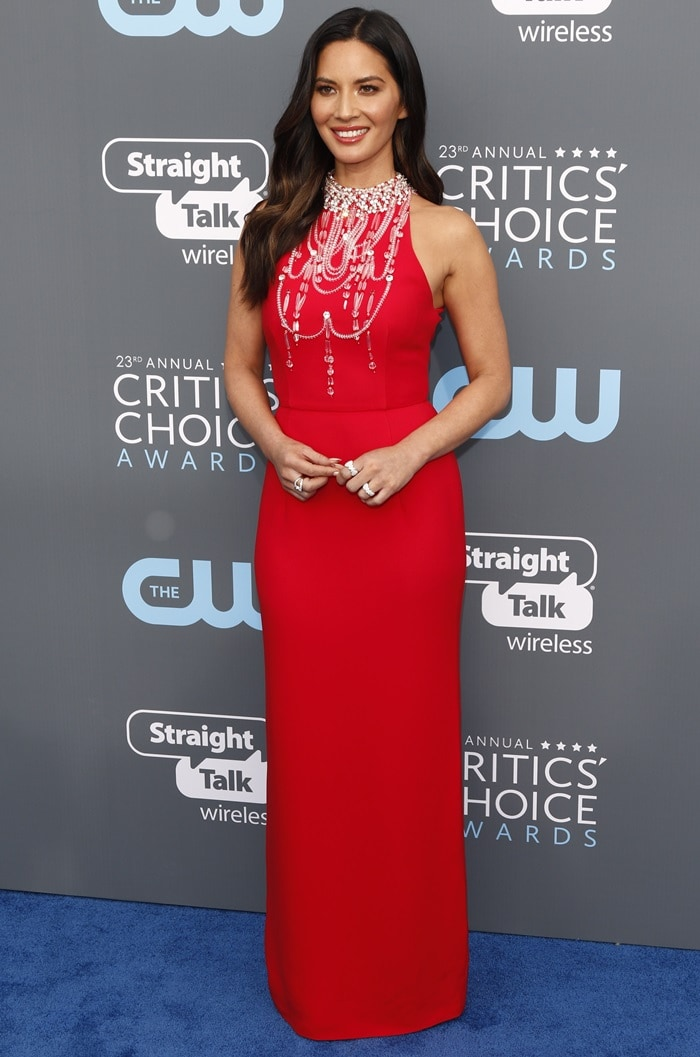 Olivia Munn wearing a red high-neck gown from Prada featuring crystal beads around the neck at the 2018 Critics' Choice Awards at The Barker Hangar in Santa Monica, California, on January 11, 2018
