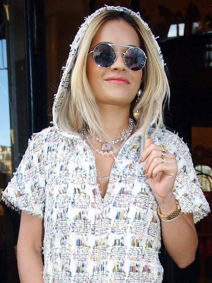 Rita Ora accessorized her look with round silver sunglasses and layered padlock-pendant necklaces