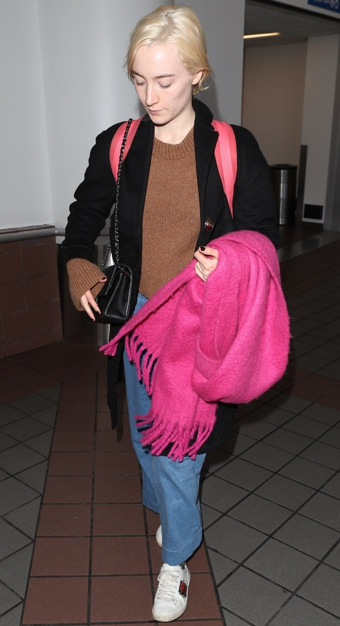 Saoirse Ronan wearing wide-legged jeans styled with a brown knitted sweater, a black woolen coat, an oversized pink scarf, and white sneakers