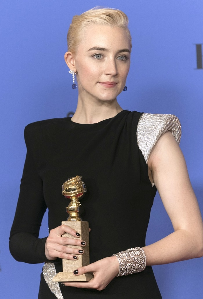 Saoirse Ronan wearing a black Atelier Versace asymmetrical gown featuring Swarovski crystal embellishments at the 2018 Golden Globe Awards held at the Beverly Hilton Hotel in Beverly Hills, California, on January 7, 2018