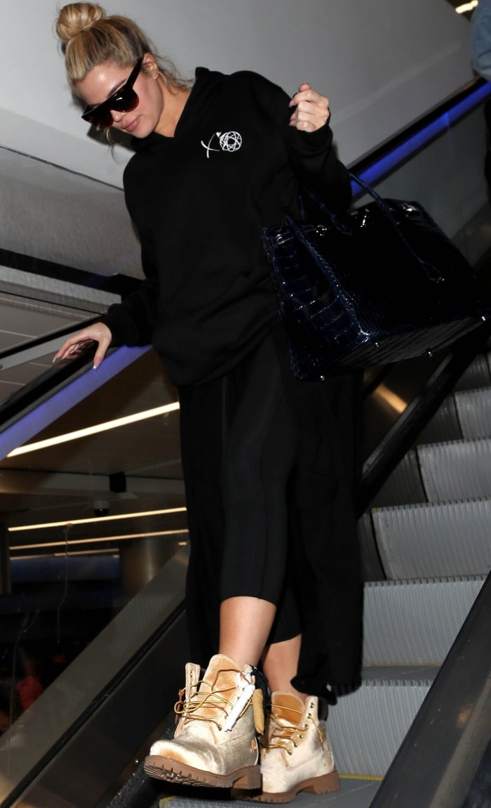 Khloe Kardashian wearing a black hoodie, cropped black leggings, and Timberland x Off-White leather lace-up boots at the Los Angeles International Airport