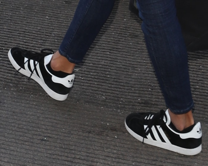 Alessandra Ambrosio wearing black and white Adidas 'Gazelle' sneakers