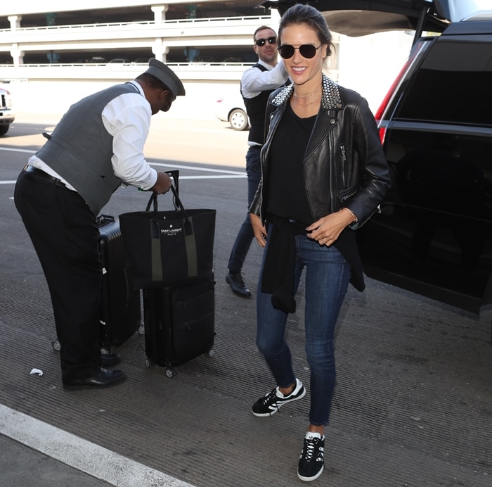 Alessandra Ambrosio embraced her rebellious side in a leather motorcycle jacket with metal studs by Nour Hammour with tight blue jeans and Adidas 'Gazelle' sneakers