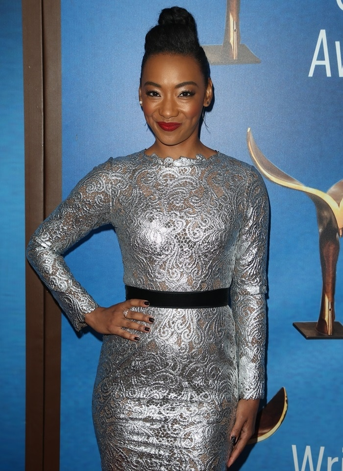 Betty Gabriel in a silver long sleeve floral lace dress from the Anaya Fall 2017 collection at the 2018 Writers Guild Awards at The Beverly Hilton Hotel in Beverly Hills, California, on February 11, 2018