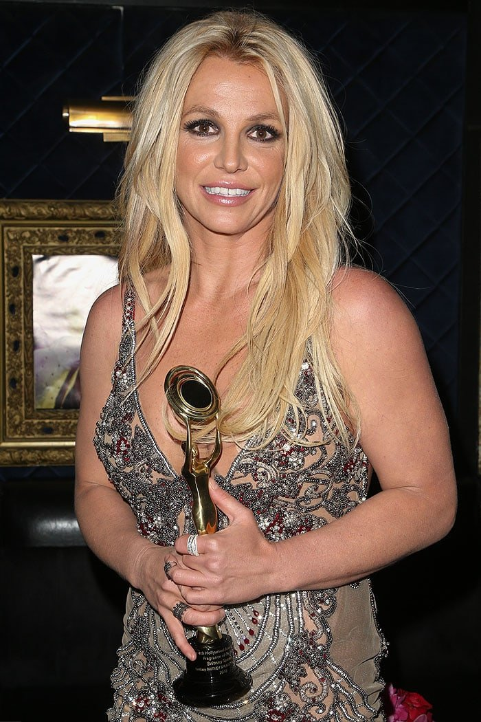 Britney Spears holding her 4th Hollywood Beauty Awards 'Fragrance Of The Year' award for her 'Fantasy In Bloom' fragrance.