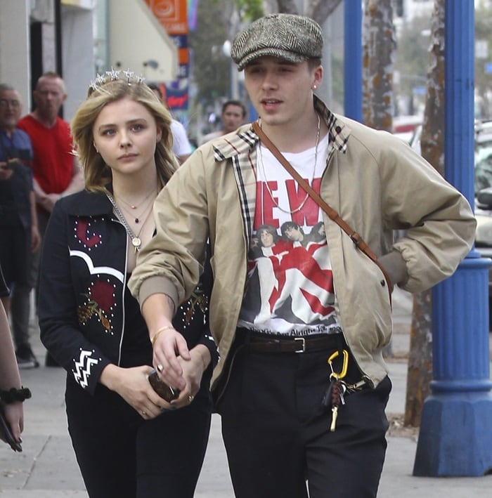 Brooklyn Beckham also looked every inch the trendsetter in ankle grazer pants, a rock-inspired t-shirt, and a dapper baker boy hat