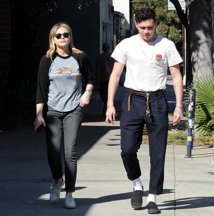 Chloe Moretz styled Citizens of Humanity jeans with Oliver Peoples sunglasses, a Doobie Brothers tee, and white sneakers from Reebok