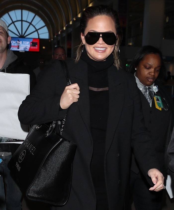 Chrissy Teigen wearing a chic mini dress and a black coat at Los Angeles International (LAX) on February 23, 2018