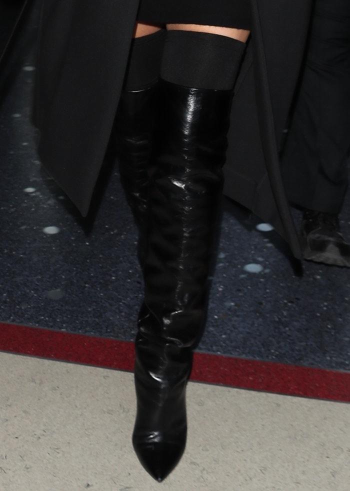 Chrissy Teigen wearing black glossed-leatherSaint Laurent 'Niki' knee boots