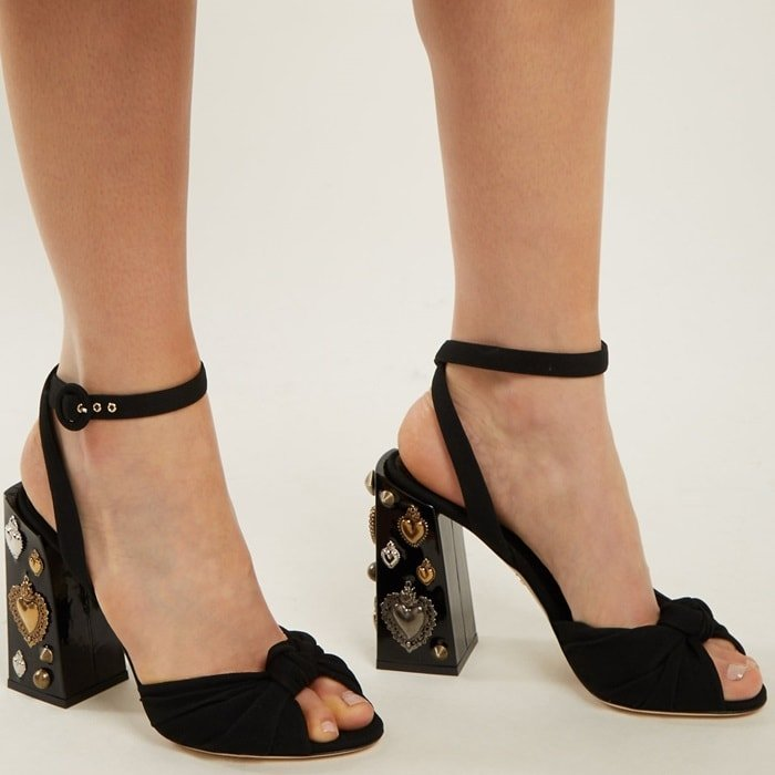 These black statement sandals are set on a towering block heel that's embellished with rustic metallic-silver and gold-tone heart, circle, and cone-shaped studs