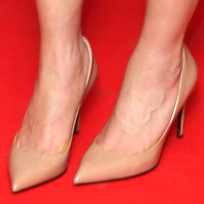 Closeup of the nude patent pointy-toe pumps on Emilia Clarke.