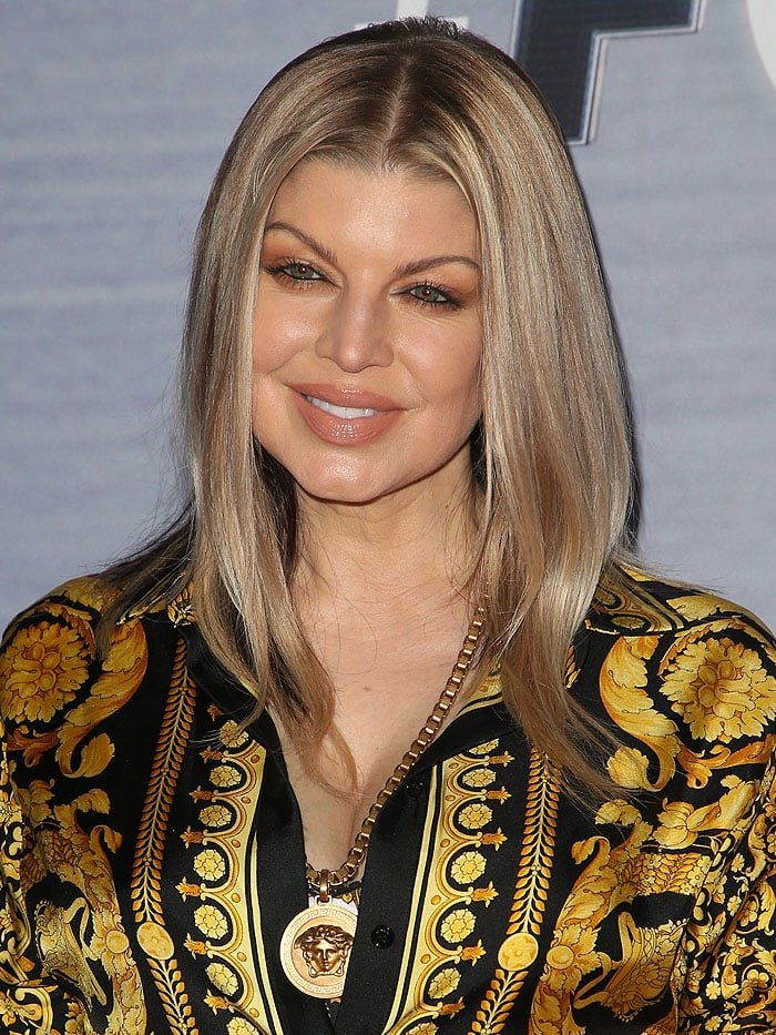 Fergie wearing a Versace gold printed satin shirt and a Versace Medusa logo pendant necklace