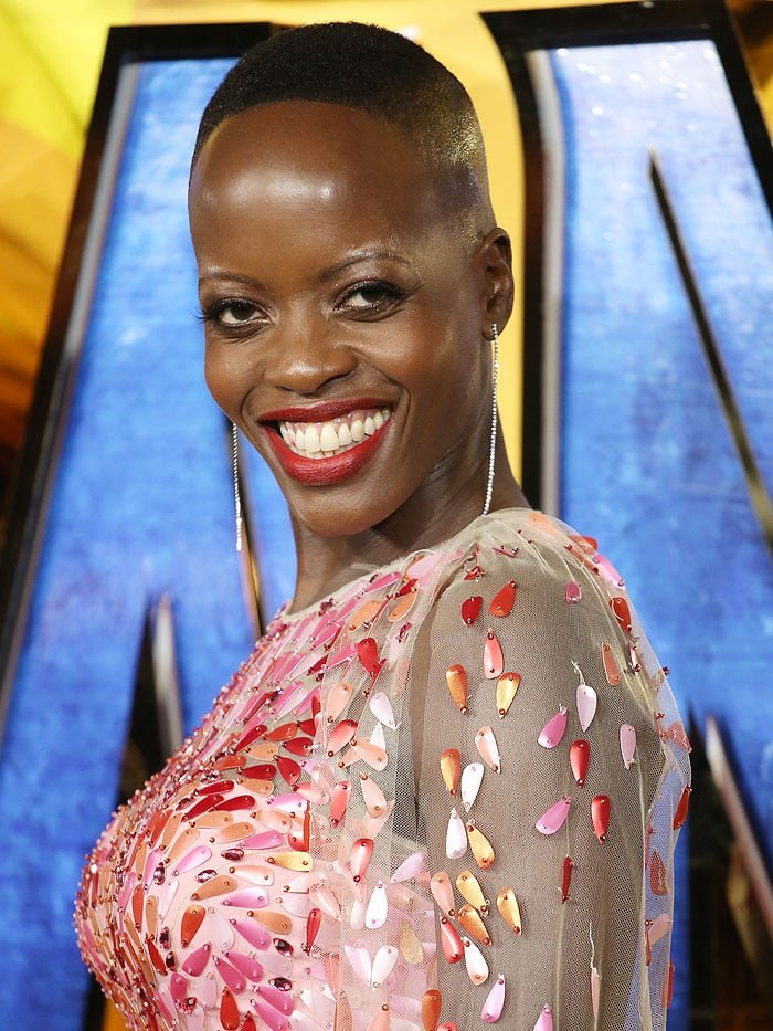 Florence Kasumba in dangling diamond-string earrings and a pink-and-red-sequined Jeny Packham gown.