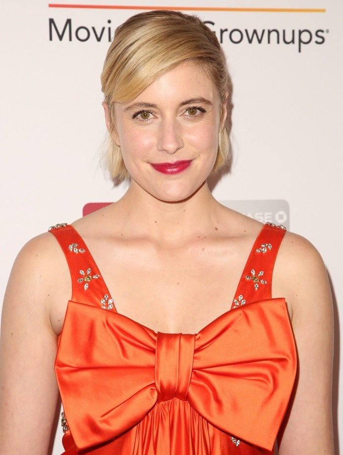 Greta Gerwig in a tangerine-colored vintage Cardinali dress featuring an oversized bow