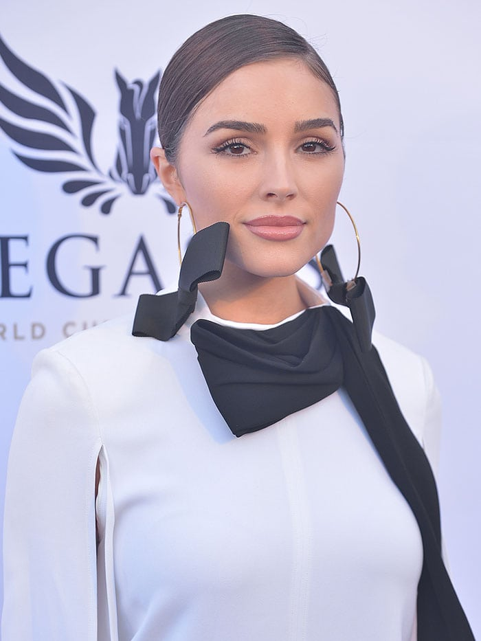 Olivia Culpo in a white Elisabetta Franchi Fall 2017 split-sleeve shirtdress with a half-draped, black pussy bow at the neck