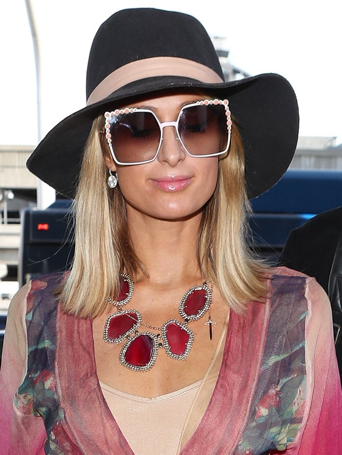 """Paris Hilton over-accessorized with a black, wide-brimmed hat, Fendi """"White Can Eye"""" embellished sunglasses, and a massiveKendra Scott """"Ava"""" pink agate necklace"""